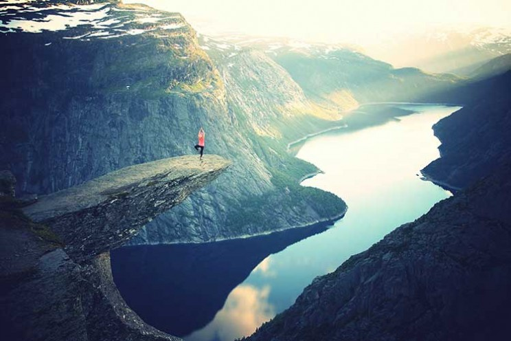 girl stretching over a cliff