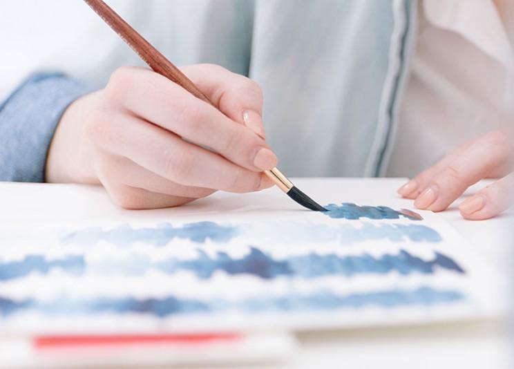 هنرمند در حال نقاشی با قلم مو