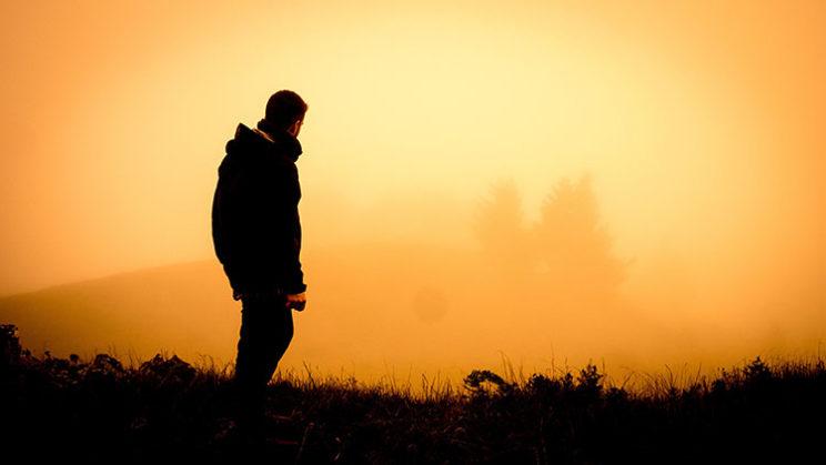 مردی ایستاده در غروب