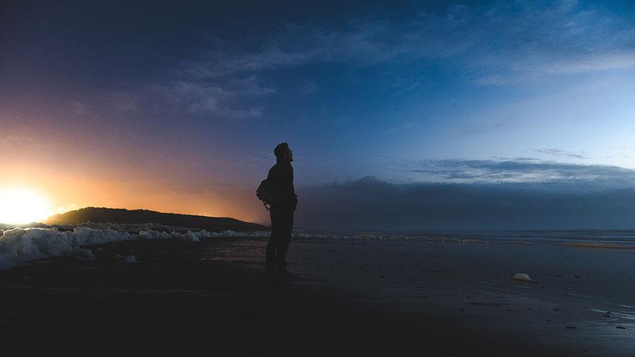 مردی میان غروب آفتاب و طلوع مهتاب در ساحل ایستاده